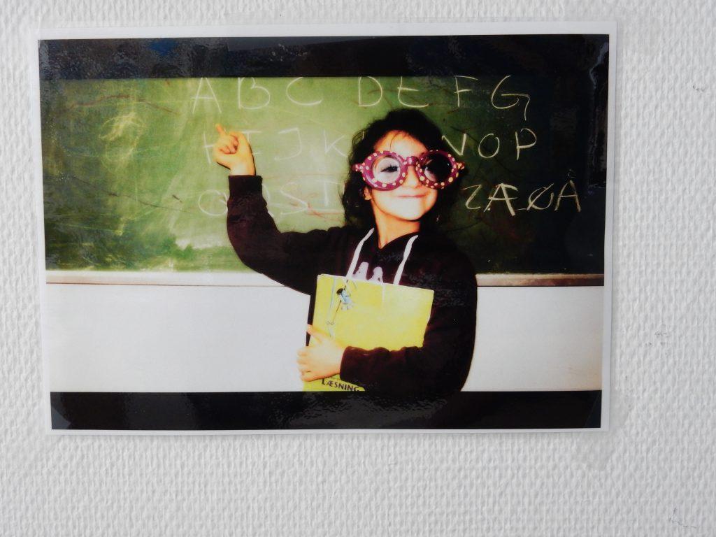 Foto af et foto af en pige foran en skole tavle