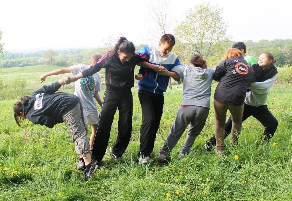 Foto af unge mennesker på en græsmark der holder armene sammen i en kæde