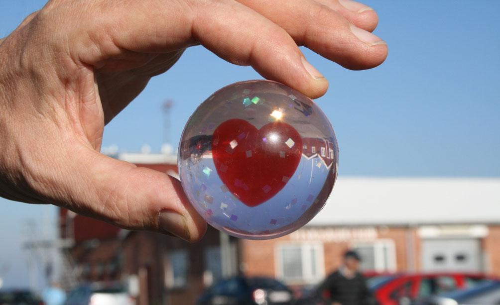 Foto af en hånd der holder en glaskugle, med et hjerte indeni