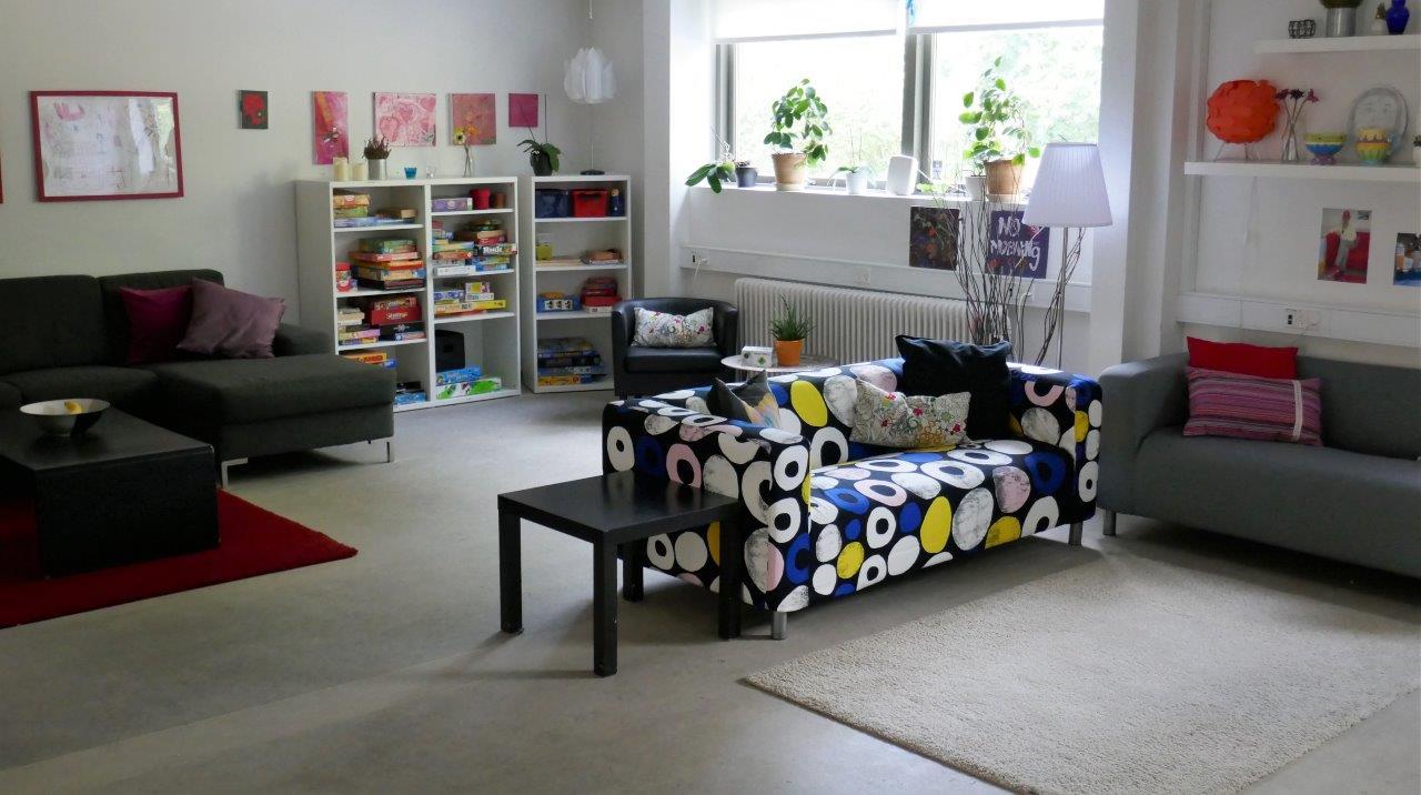 Foto af fra børnehusets stue og hyggerum med sofaer og spil