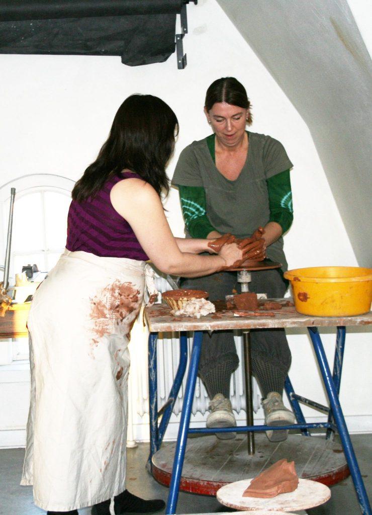 To Kvinder arbejder med ler, ved en drejebænk